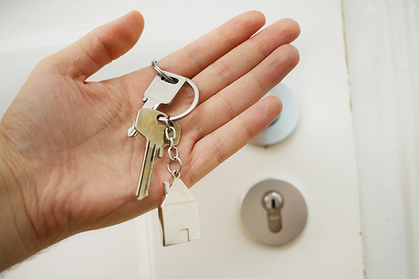 Woman holding house keys outside of her securely locked home