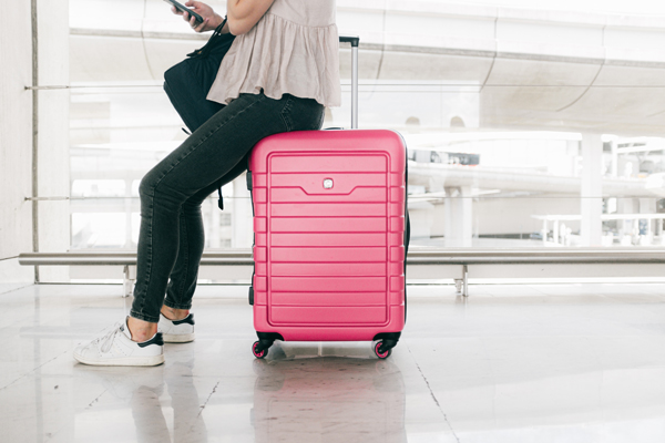 Woman sitting on a suitcase with luggage security