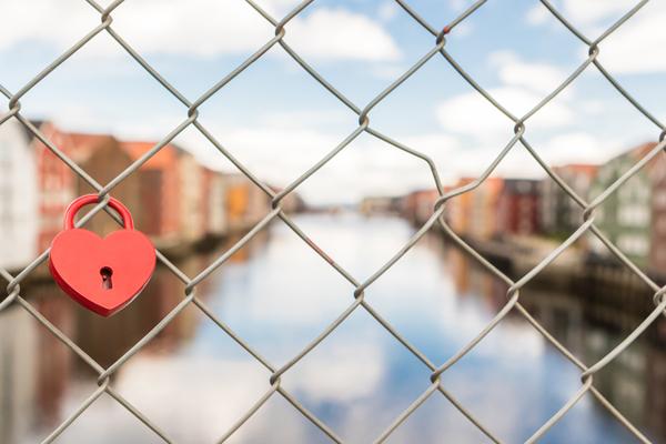 heart shaped lock affixed to a romantic love lock bridge
